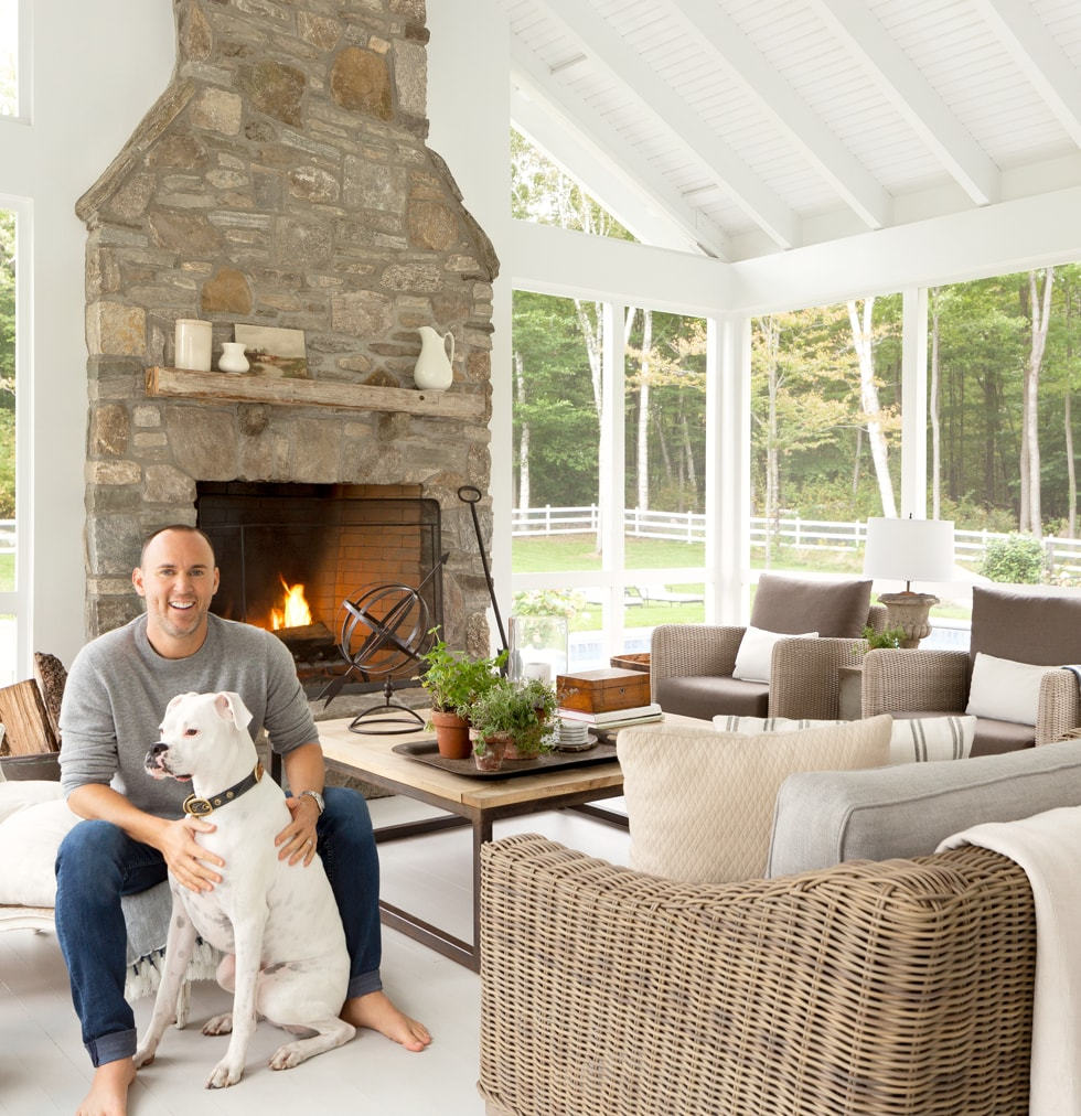 Joshua Smith petting a dog in a living room with a fireplace