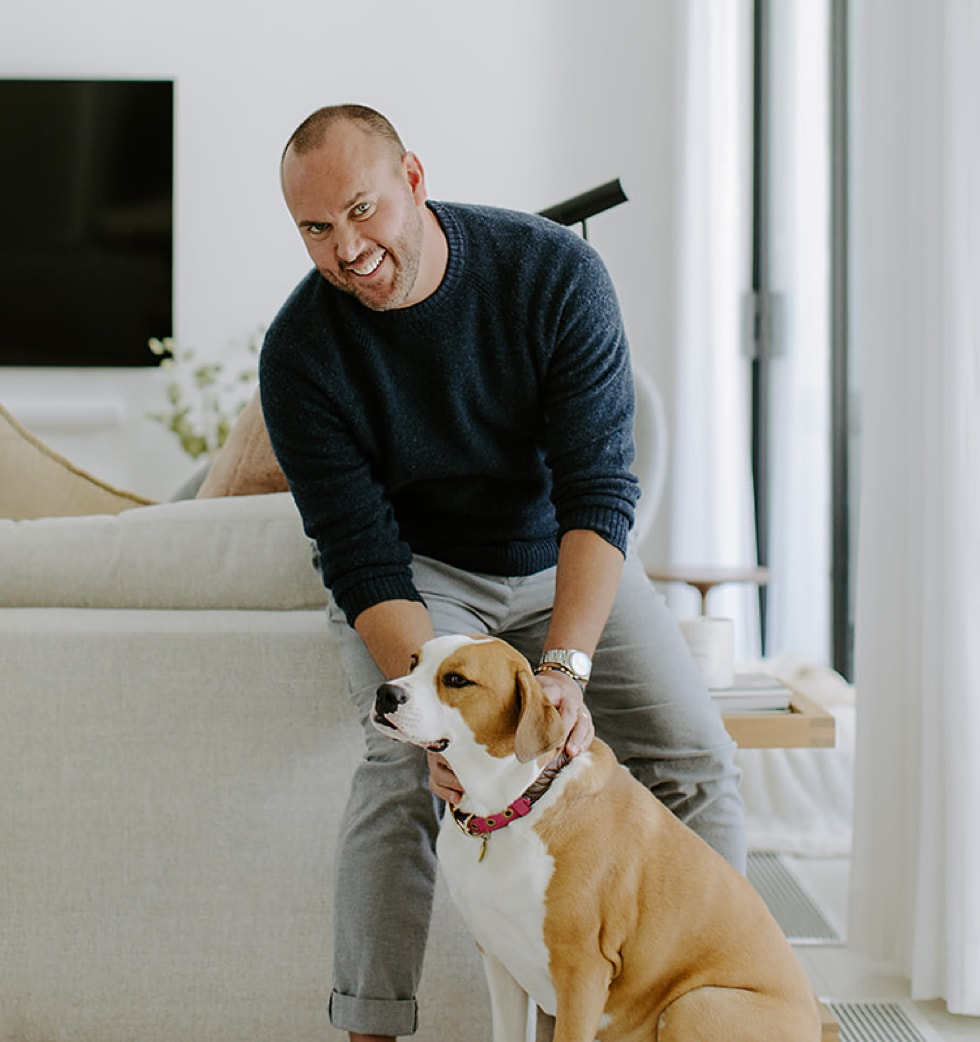 Joshua Smith petting a dog while leaning on the back of a couch