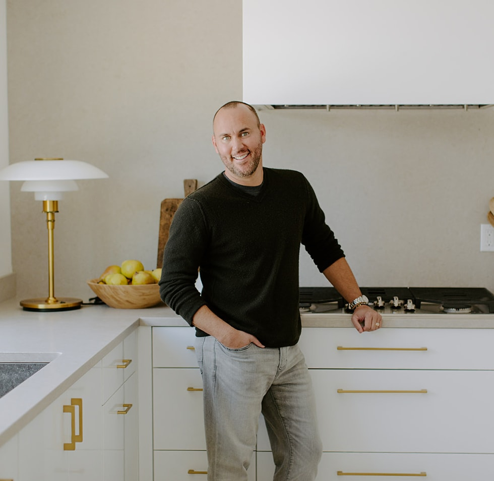 Joshua Smith standing in front of modern white kitchen counter