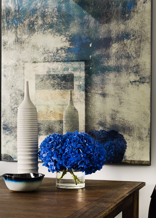 Table with vases and art on wall behind it