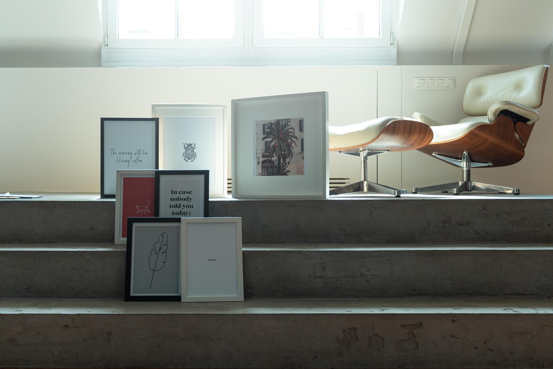 Poster aus unserem online Shop stehen auf Treppe mit Sonnenlicht.