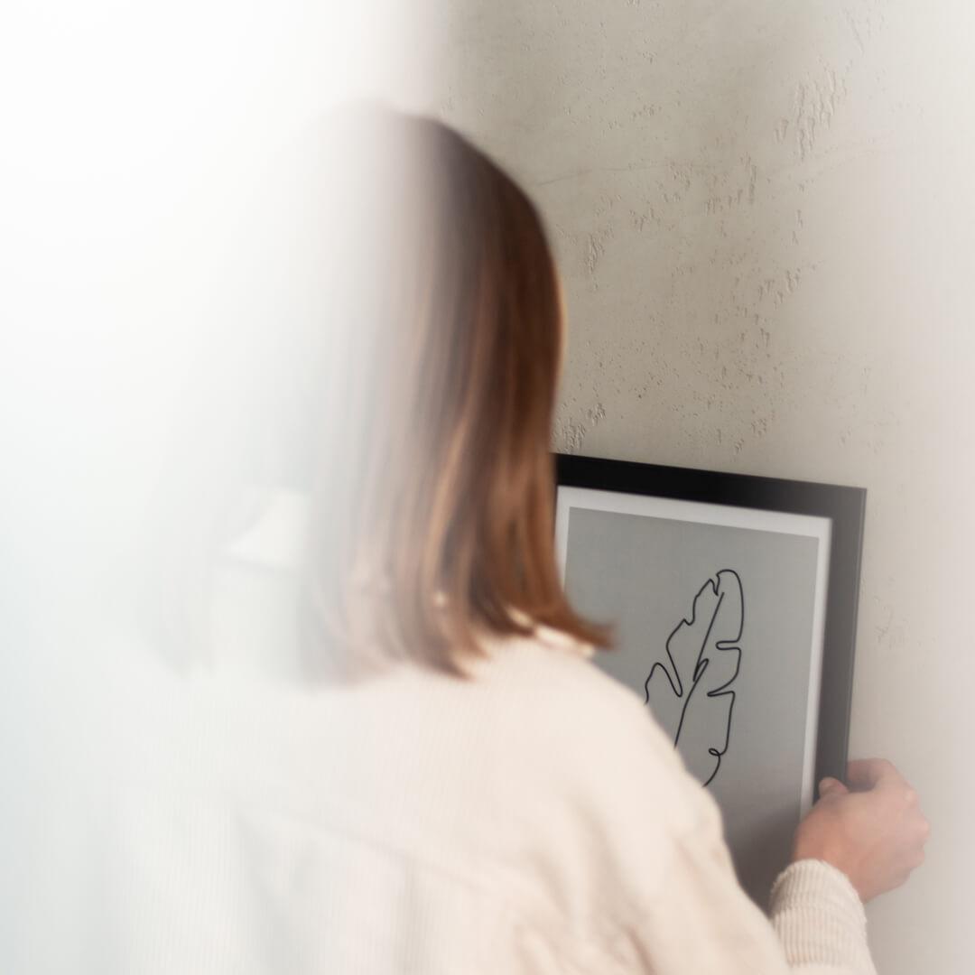 Frau hängt gerahmtes Poster  aus unserem online Shop auf.