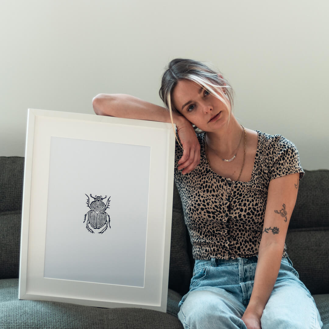 Frau mit gerahmten Käfer Poster aus unserem online Shop.