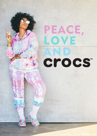 Woman wearing tie-dye outfit with matching tie-dye crocs