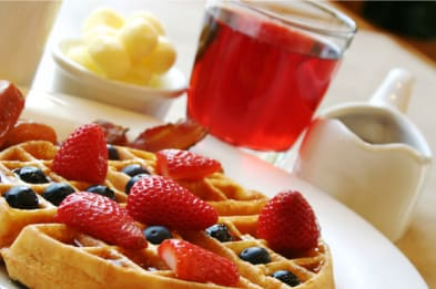 Waffles with berries and a cup of juice