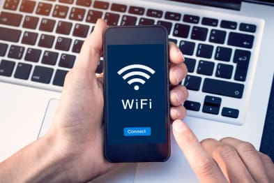 Hand holding a mobile phone connecting to WiFi
