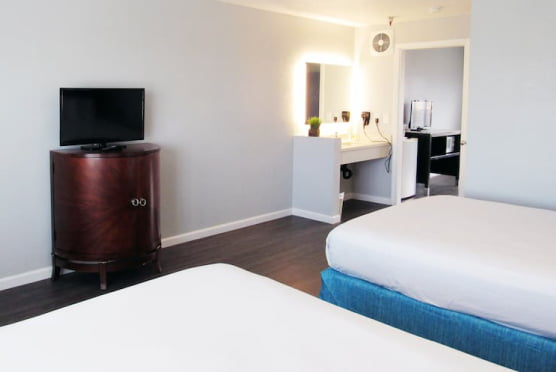 Two beds, with a LCD TV and vanity