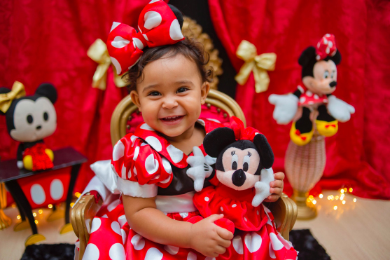 Girl dressed as Minnie Mouse holding a Minnie mouse's plushie