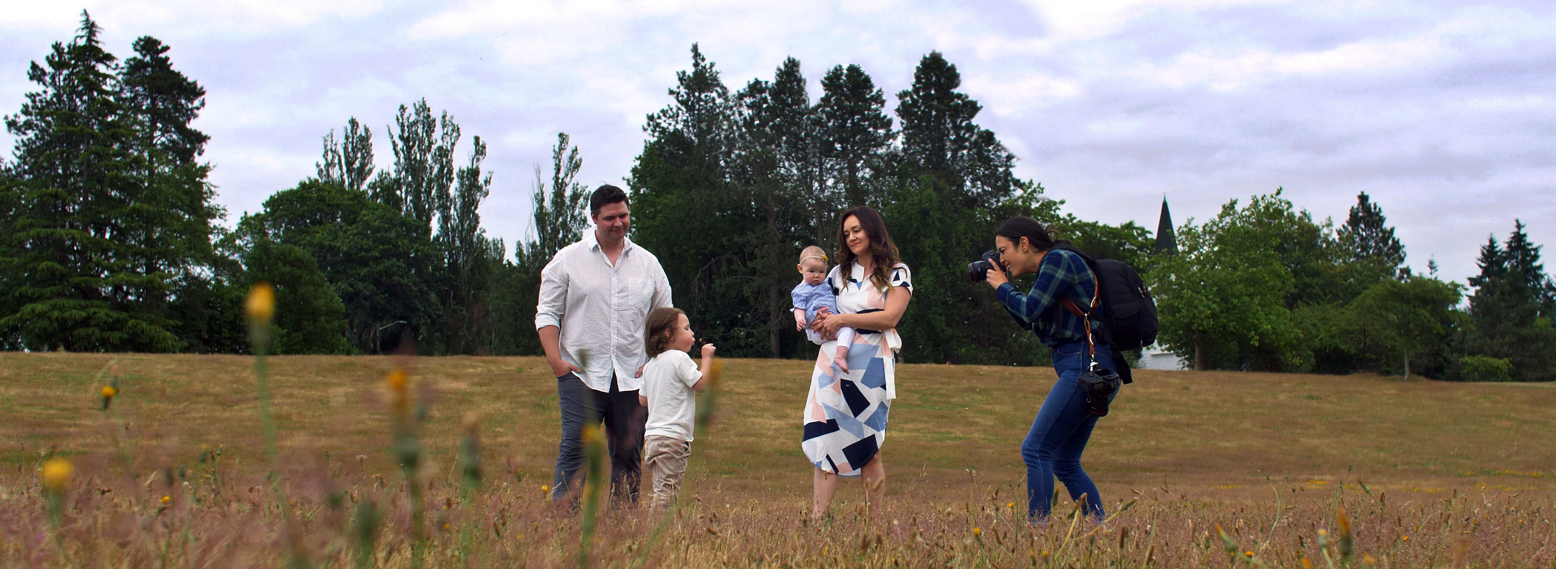 Family wearing white and blue matching outfits in a field getting photographed by ShootProof photographer Elena Blair