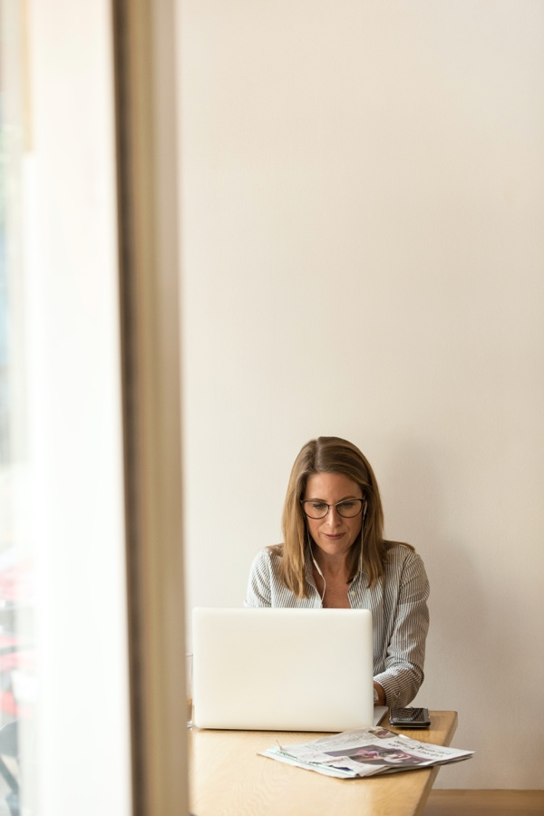 A woman seated looking at her computer.