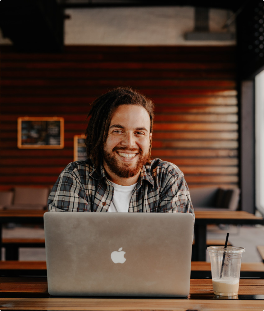 A smiling person sits at a desk with a laptop in front of them