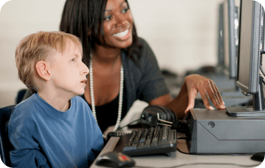 woman assisting young child in front of a computer