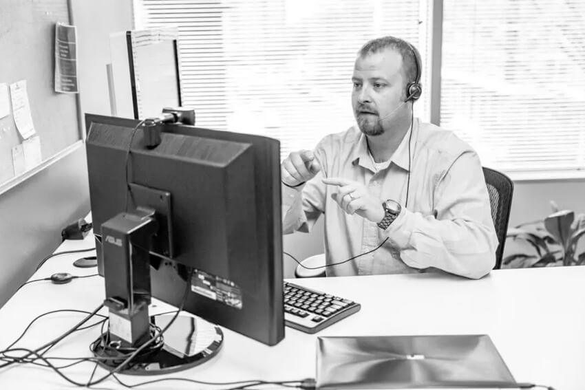man providing information technology support in front of computer
