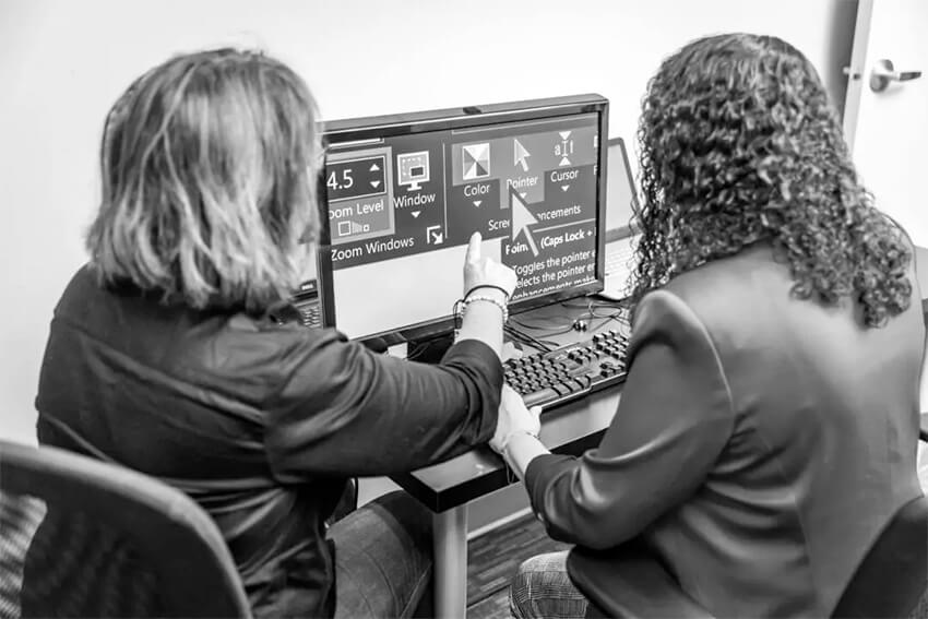 woman using computer while another woman points at the screen
