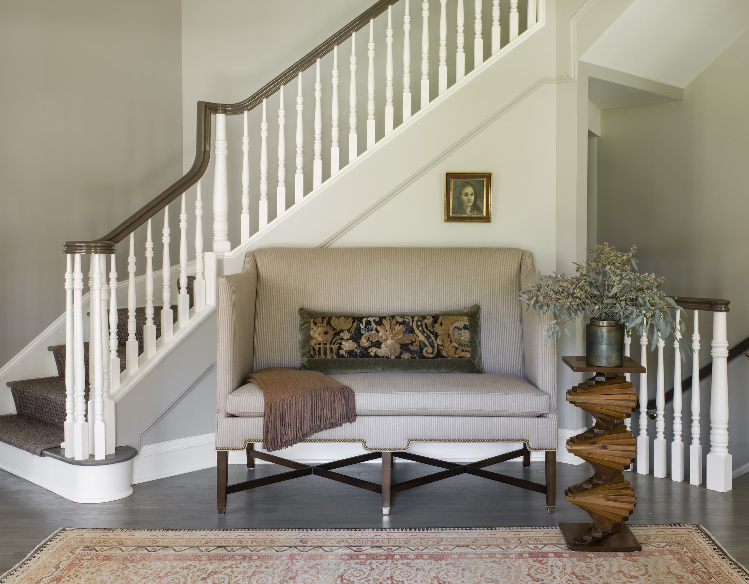 Sofa and table in front of a white staircase.
