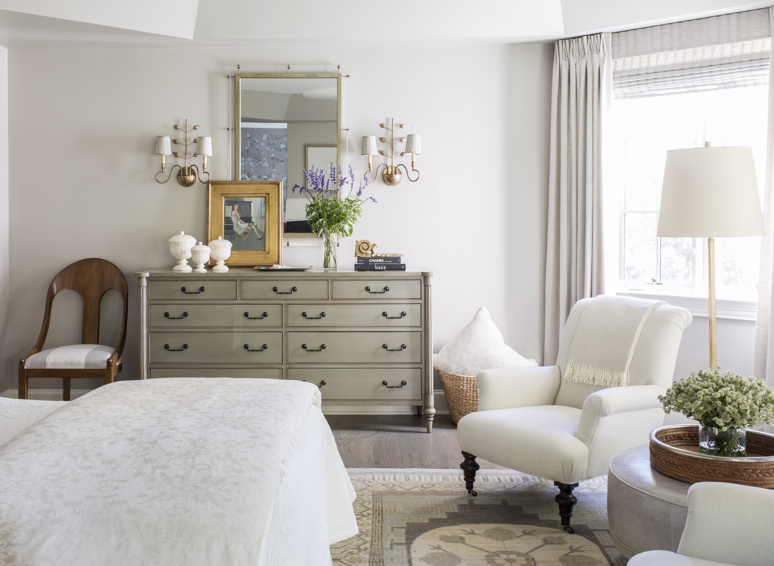 White lounge chair and dresser in a bedroom.
