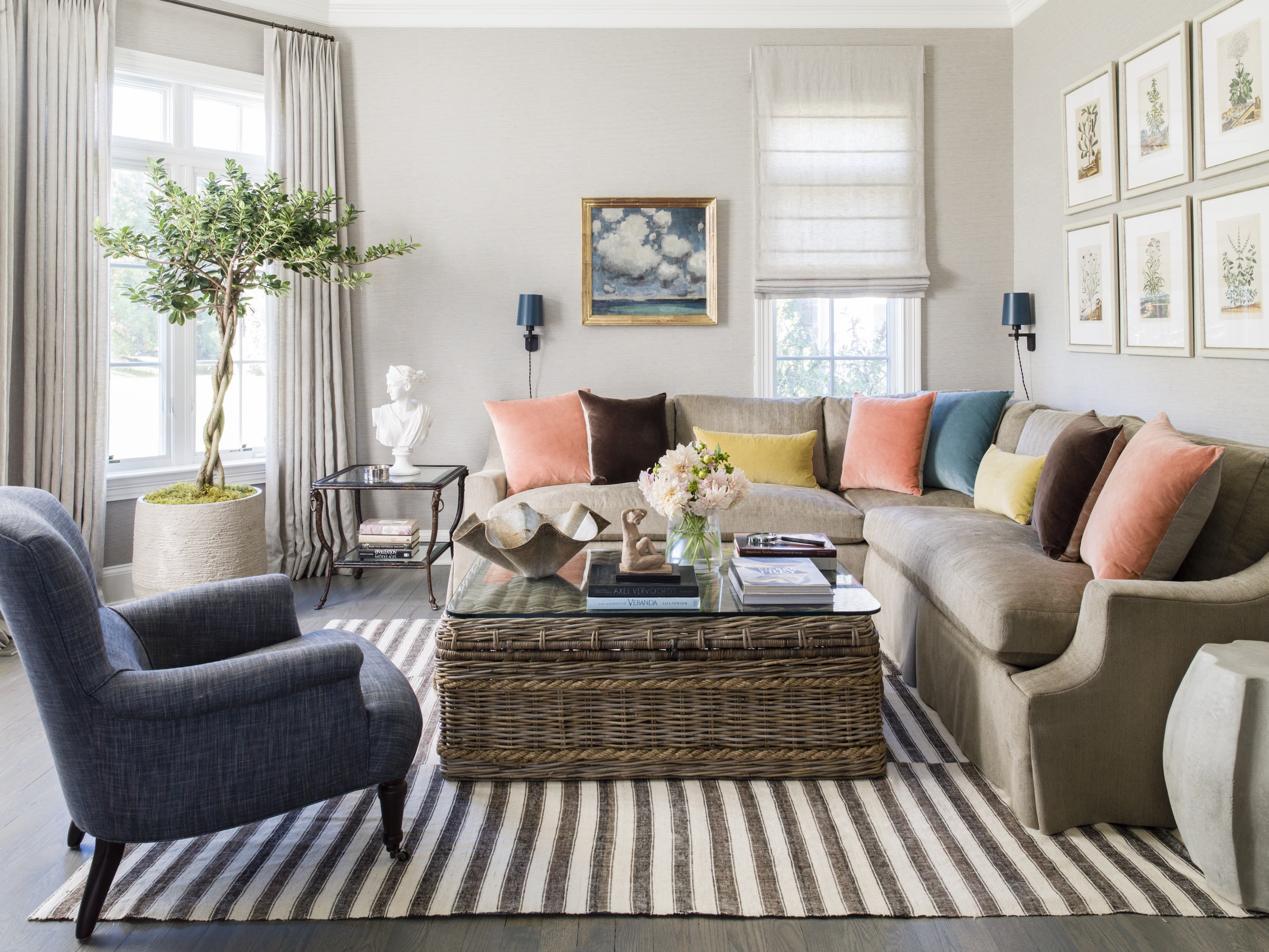 Living room with large sectional holding colorful pillows, a coffee table with books and fresh flowers, and a lounge chair.