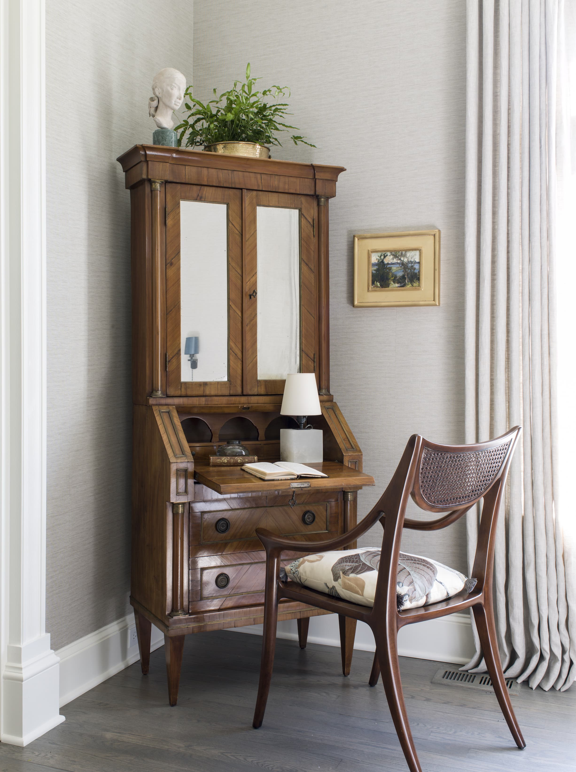 A corner cabinet with a pull-out note desk and an antique chair.