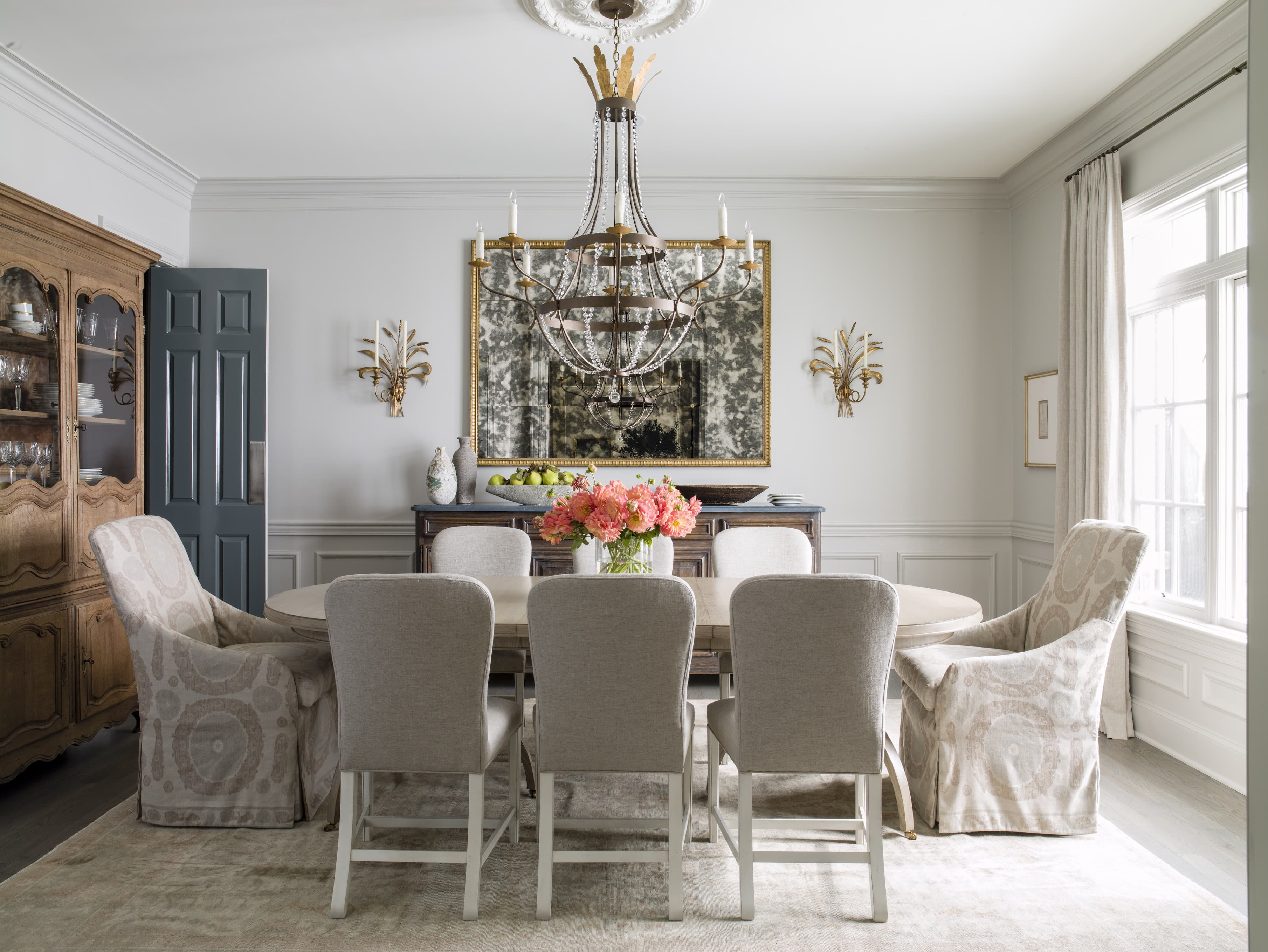 A dining table with fresh flowers and a large chandelier hanging overhead.