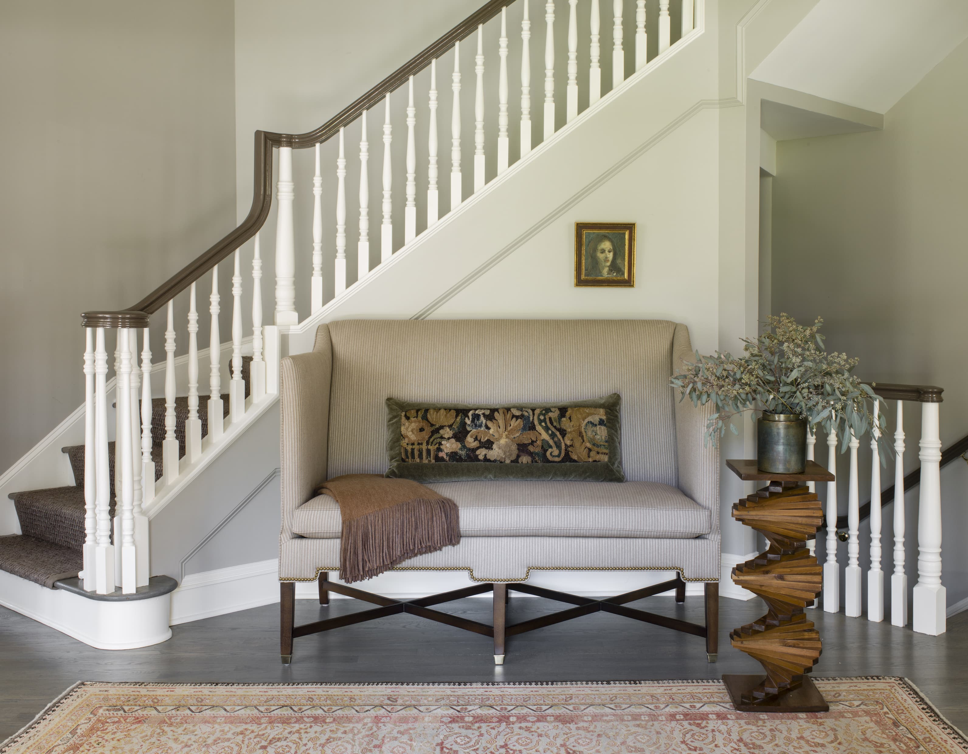A sofa in front of a white staircase.