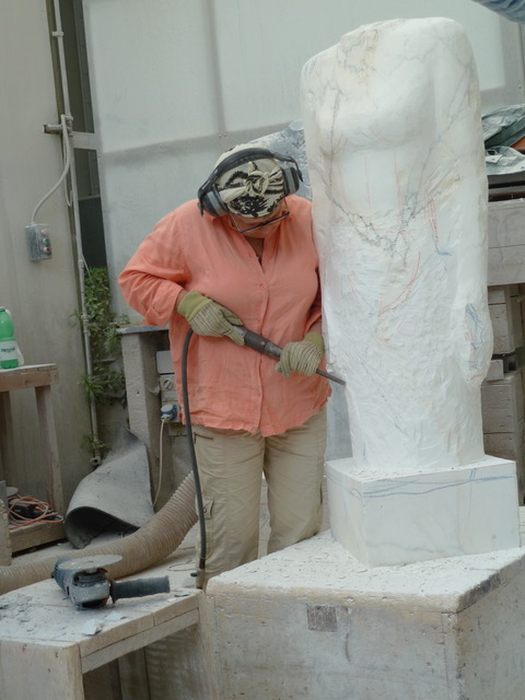 MJ Anderson at work, sculpting a large marble bust in her studio.