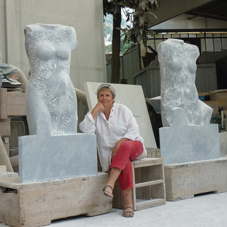 Mary Jo Anderson in her Carrara, Italy marble studio, posing with carved torsos