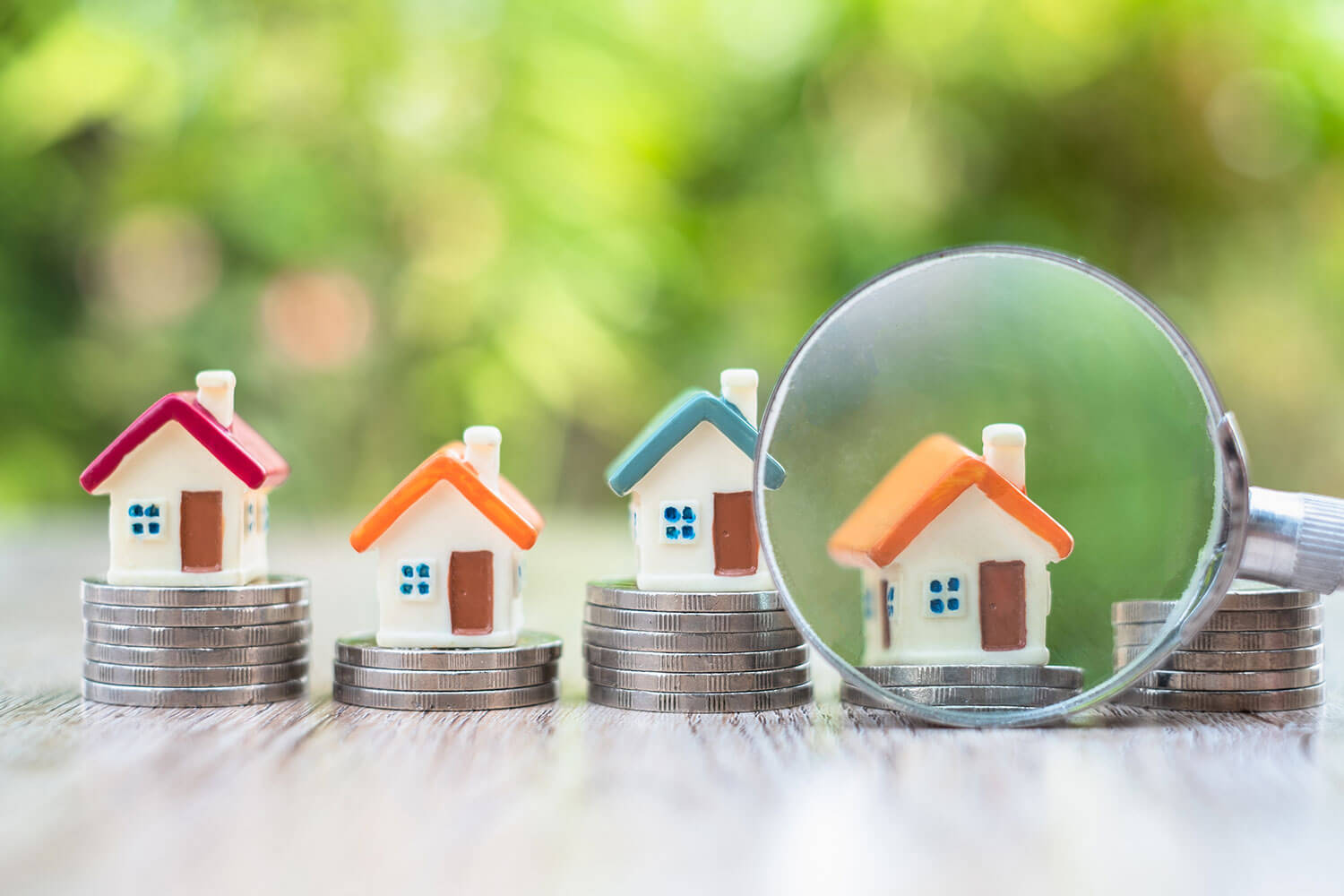 Tiny home figures on top of coins; magnifying glass centered on one. Minneapolis Exclusive Buyer Agents | The Homebuyers | MLS MN