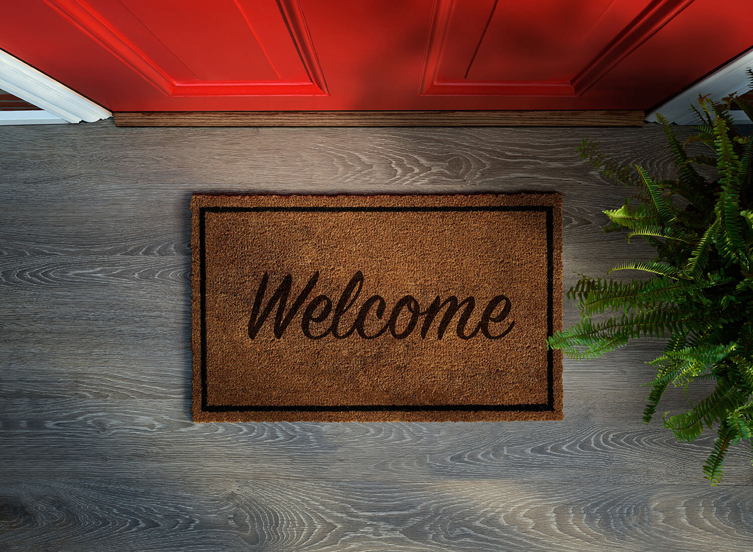 Welcome mat in front of red door. Buying a house can be complicated, let The Homebuyers help you find your dream home | MN EBA