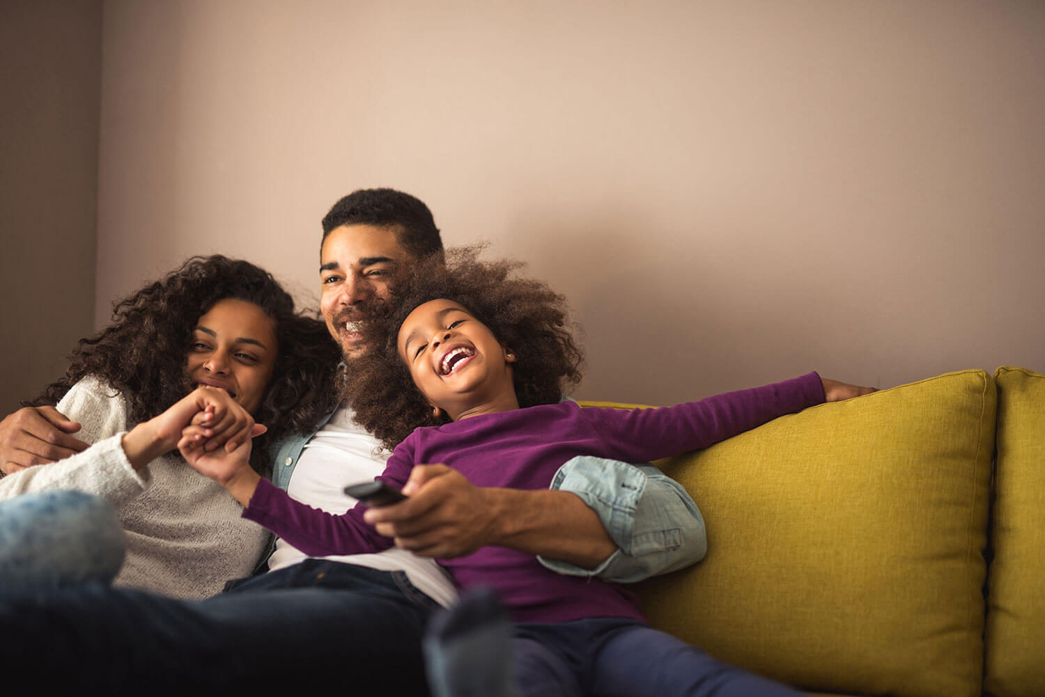 Happy family relaxing on the couch in their new home that was purchased with Minnesota exclusive buyer agents, The Homebuyers