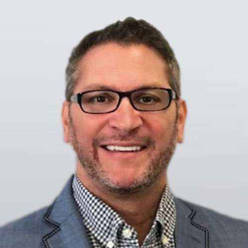 Photo of man with glasses, button down & suit jacket. Ron Jensrud, real estate & buyers agent, team member of The Homebuyers.