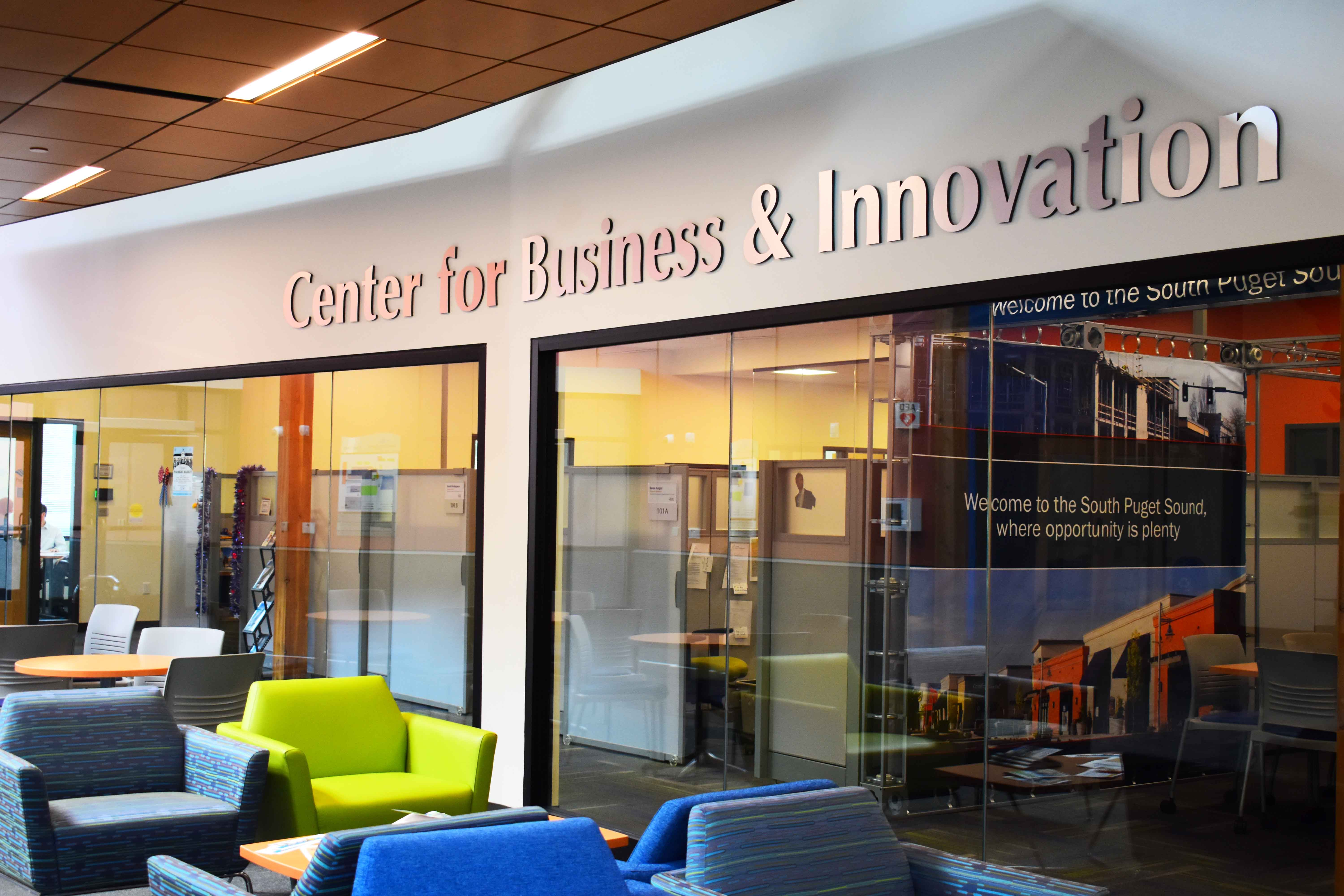 The lobby of the Center for Business and Innovation. There are empty chairs in front  of windows with the name of the center above them.