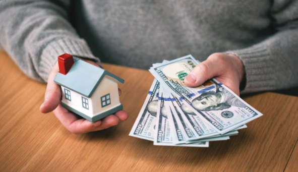 A cash house buyer holding a figure house in one hand and cash in an other
