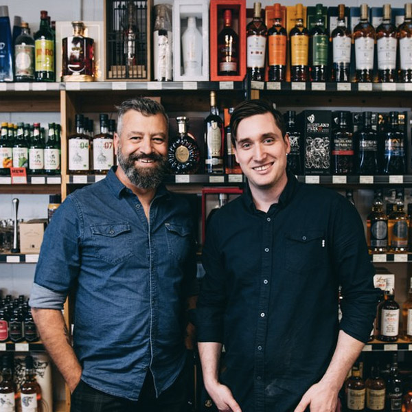 A middle aged man with a beard and a young man stand in front of 5 shelves filled with bottles of alcohol