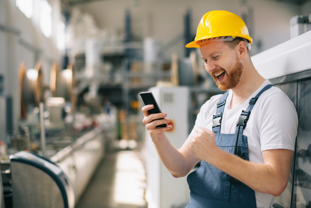 a happy construction worker looking at the mobile phone