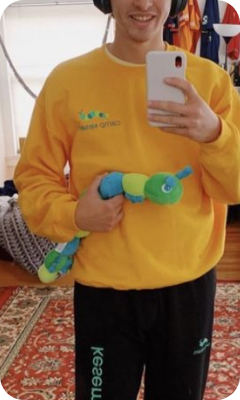 A person wearing a bright yellow Camp Kesem sweatshirt whilst holding their caterpillar mascot soft toy.