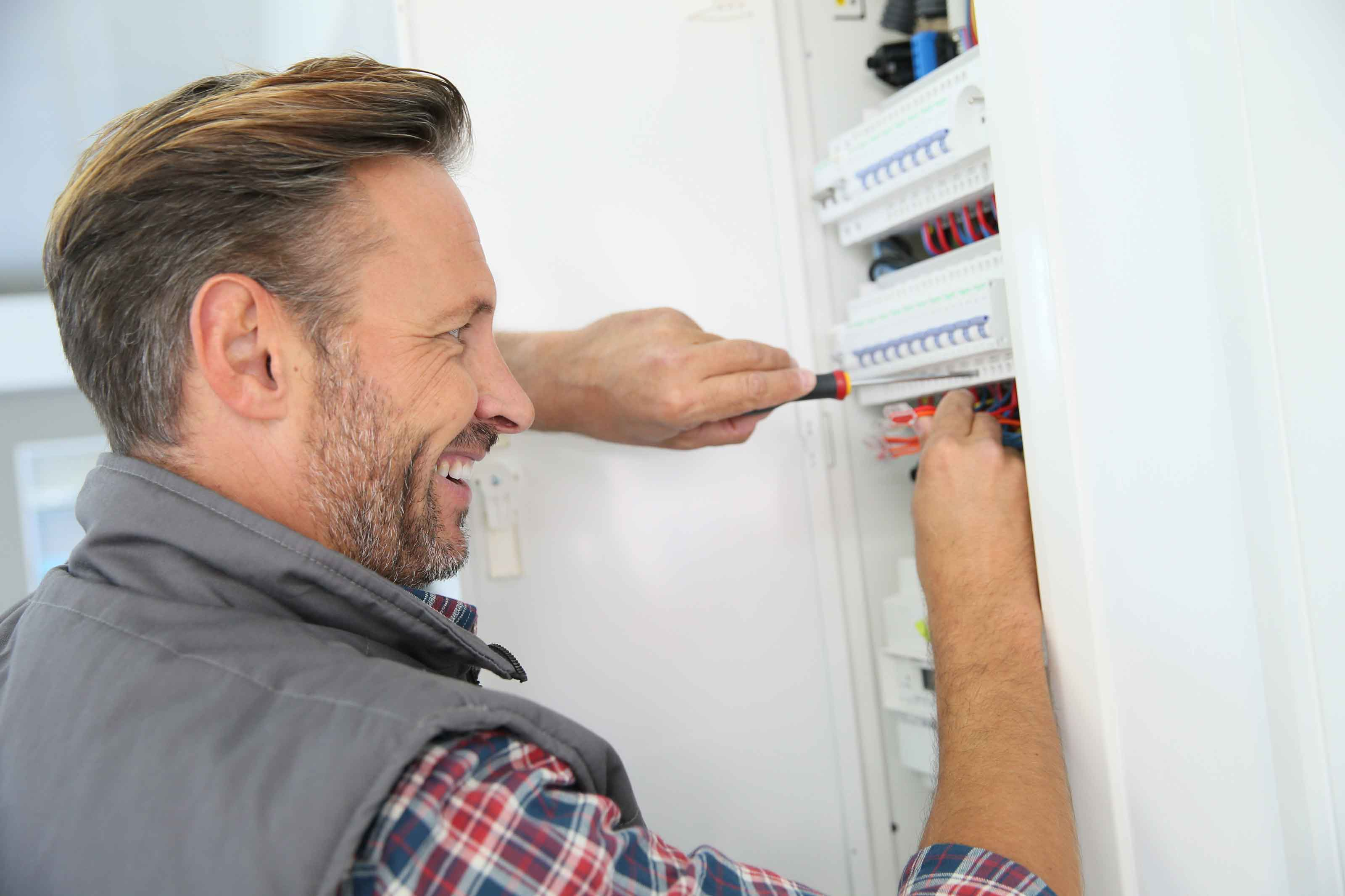 A happy electrician working on a fuse box