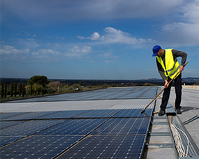 A man on a roof cleaning a solar panel