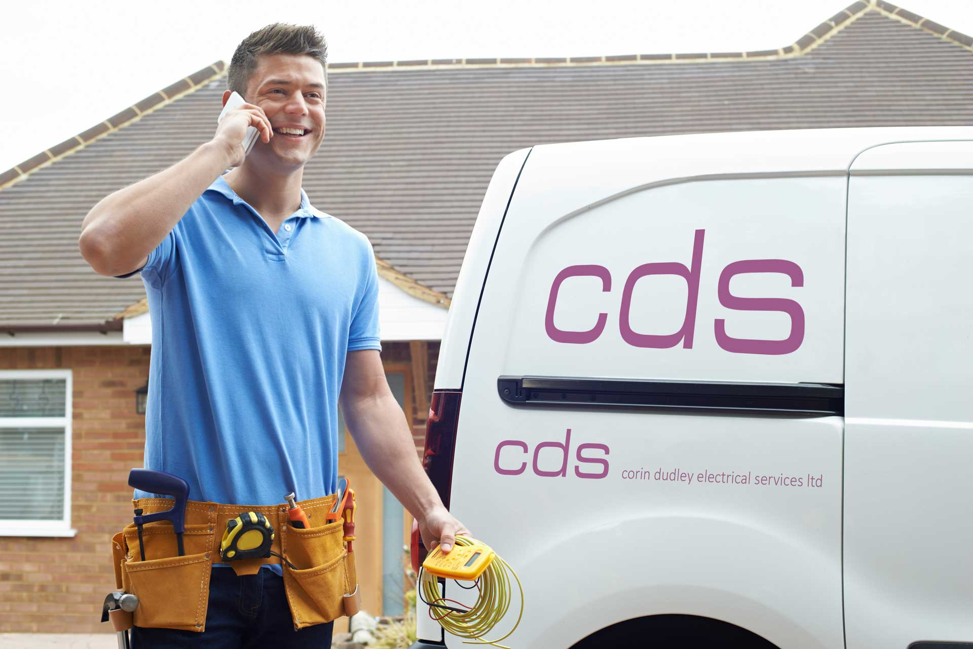 A CDS Electrical engineer talking happily on his phone by his van