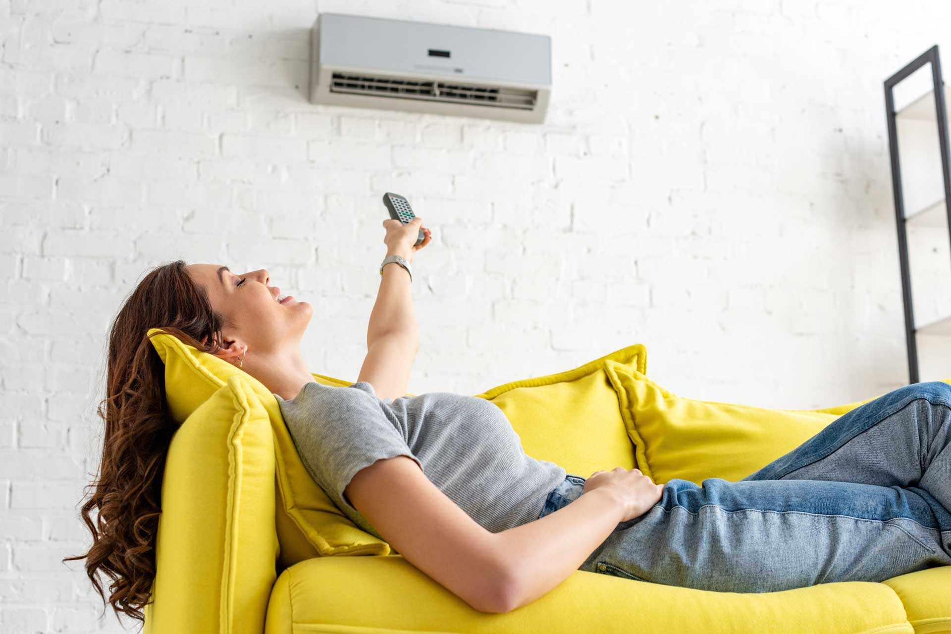 woman lying on the sofa controlling the air conditioning with a remote