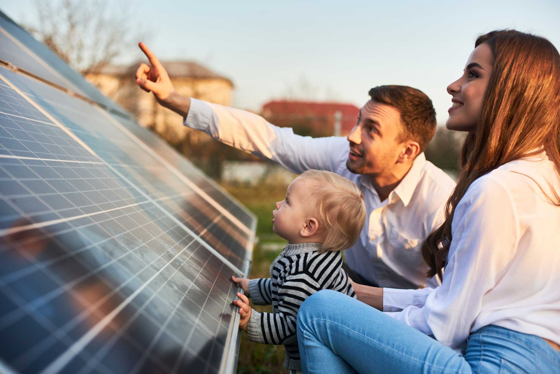 Young family looking at solar panels outside their home