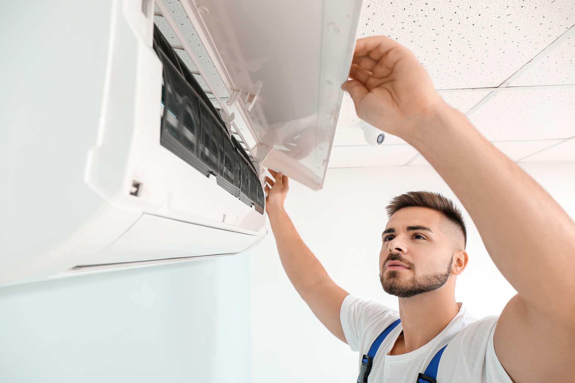 Air conditioning engineer looking into a wall mounted air conditioner