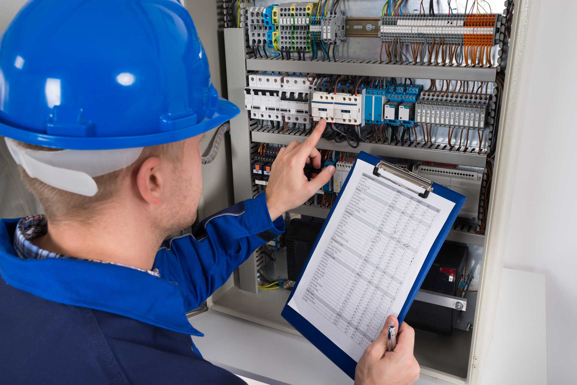 Electrical engineer testing a fuse box for faults