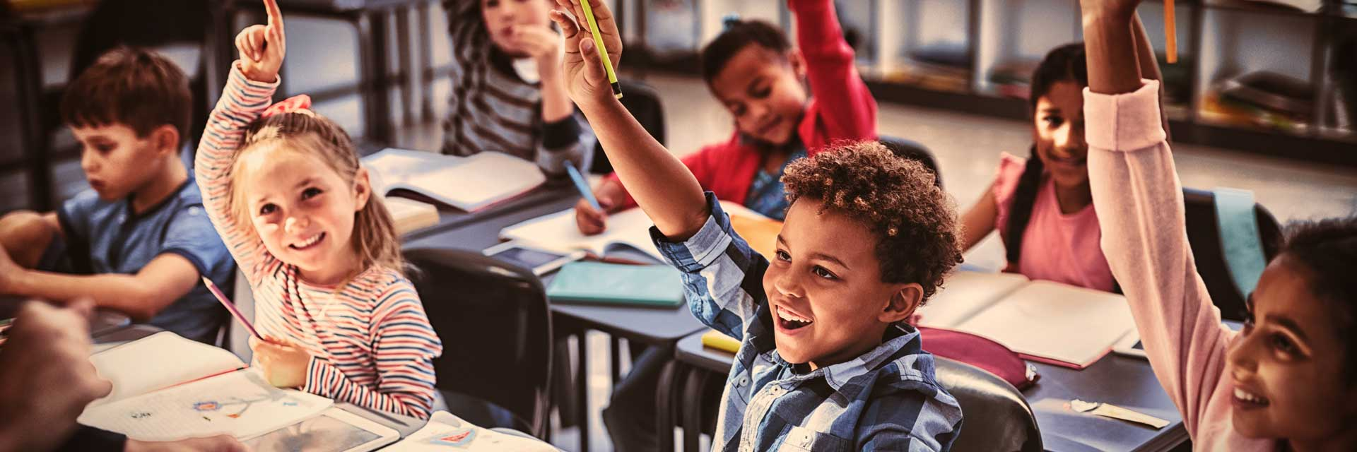 Children in a classroom with their hands up
