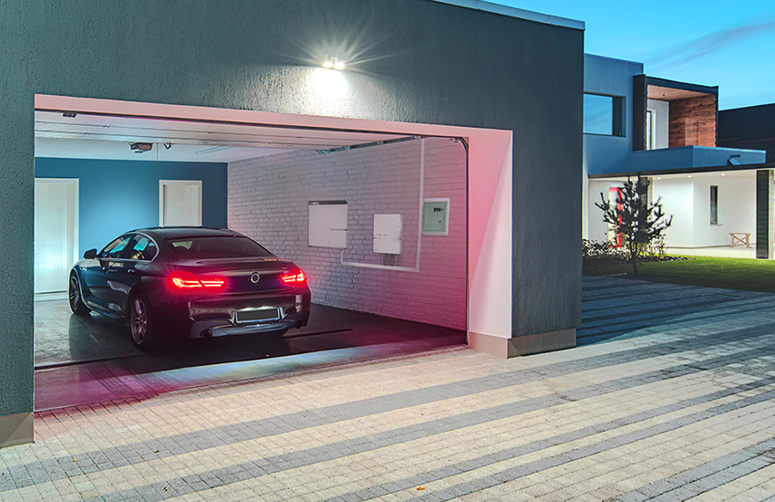 A modern garage with a car inside being electrically charged