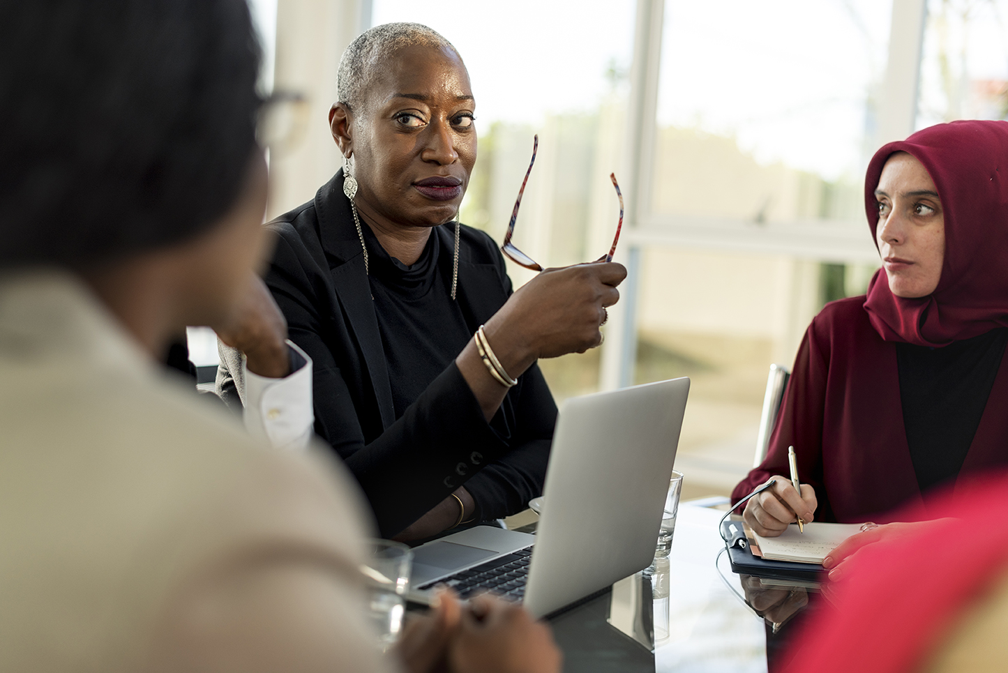 A middle-aged black woman professional leading a meeting with a multicultural and multiracial working group