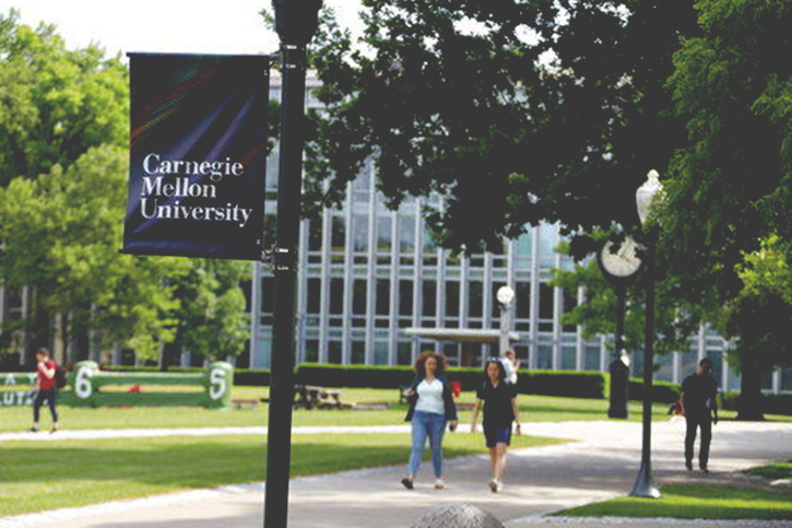 An image of the campus quad of Carnegie Mellon University with students walking to class