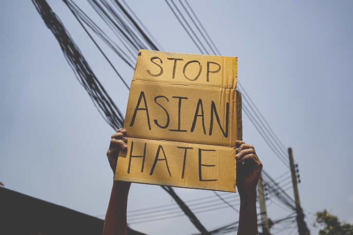 """A photo of a person holding a homemade sign which reads """"Stop Asian Hate"""""""