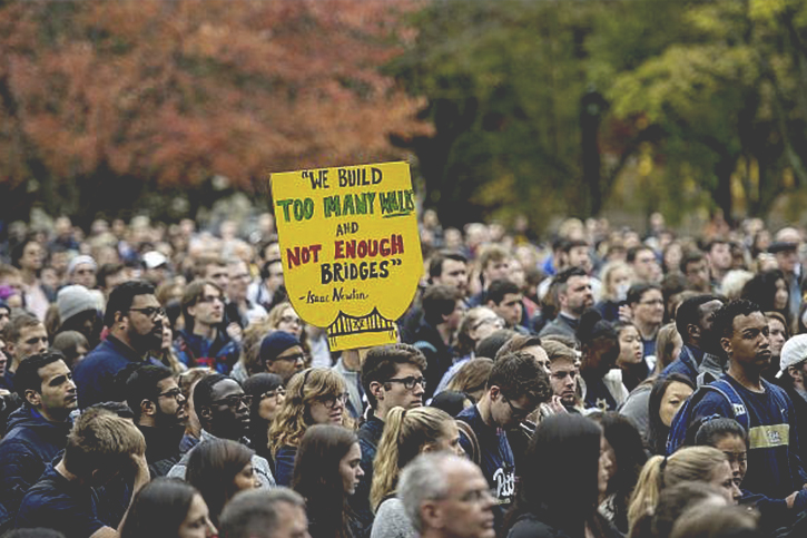 """Photo of a large group of people gathered for a protest in Pittsburgh. A sign can be seen which reads """"We build too many walls and not enough bridges"""""""