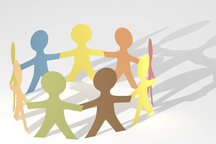 A stylized image of paper cut-out people of many colors joining hands in a circle