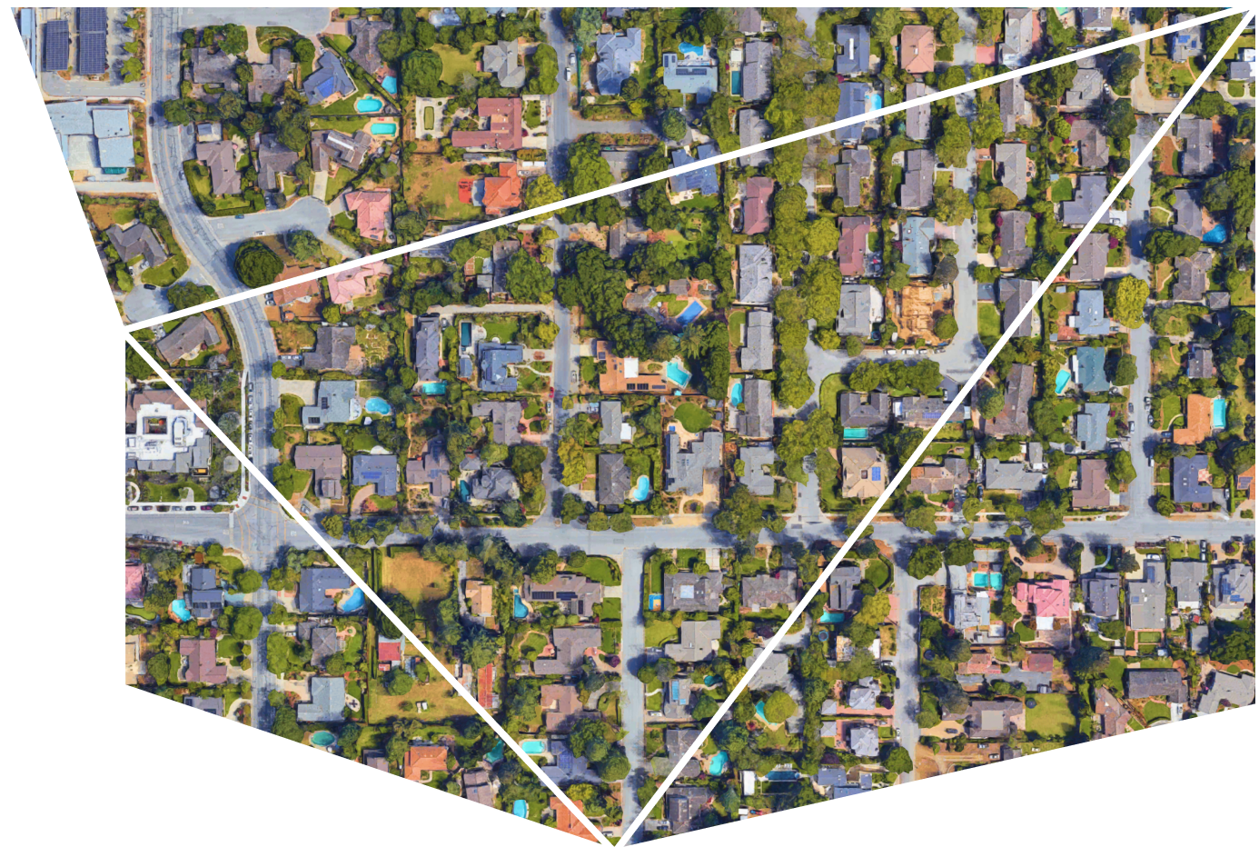 An aerial view of a suburban neightborhood with rooftops, deciduous trees, and backyard swimming pools.